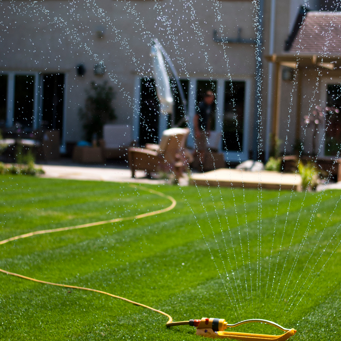 A photograph of a sprinkler watering a newly laid lawn