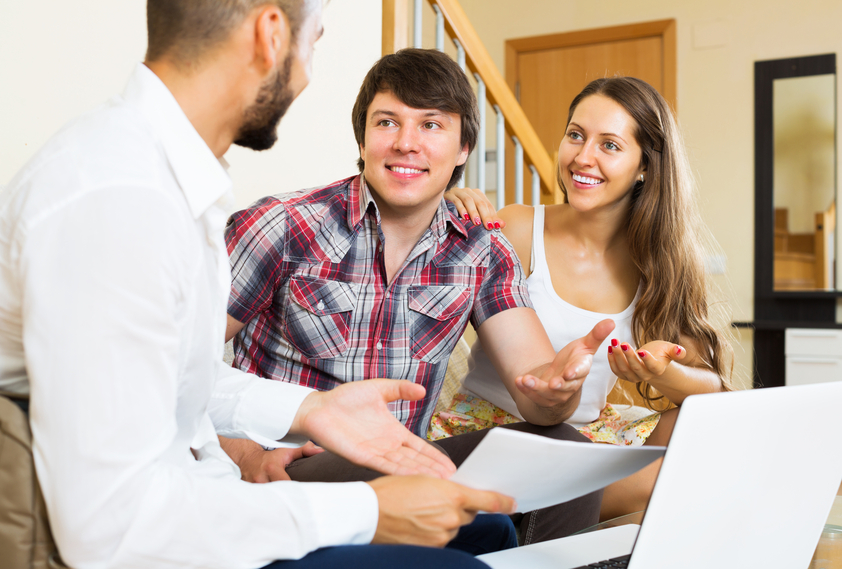 Positive couple and salesman talking cheerfully about purchase at home