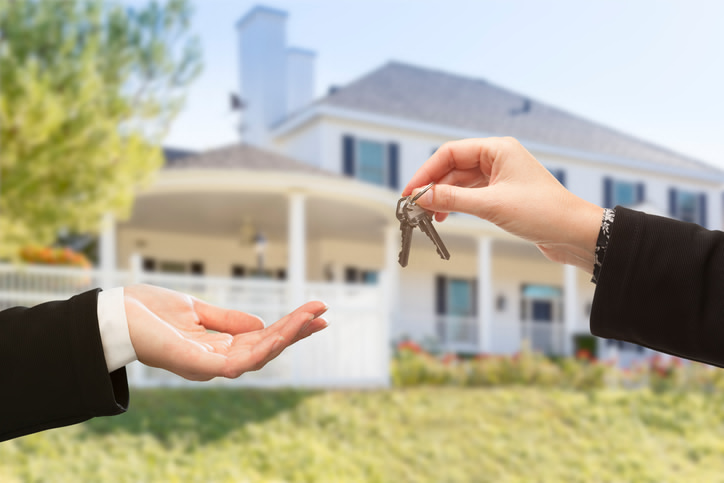 Real Estate agents handing key to client