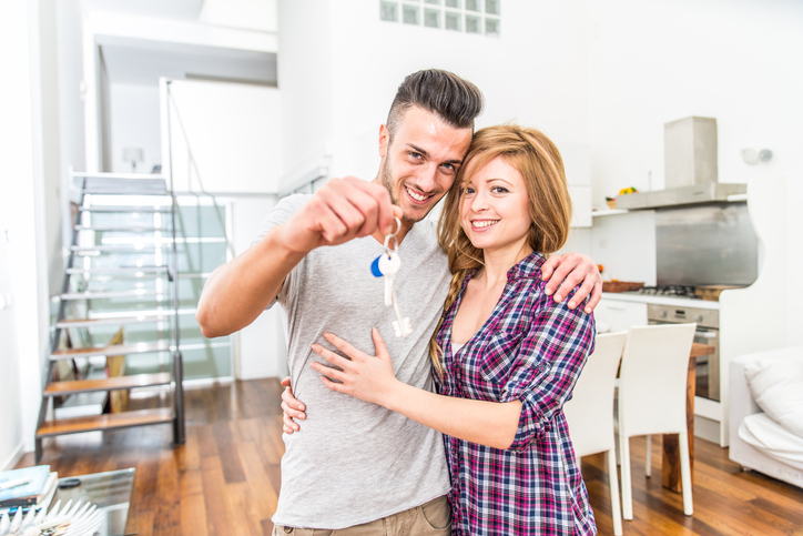 Couple buying a new house - Young cheerful partners moving to a new flat and starting to live together