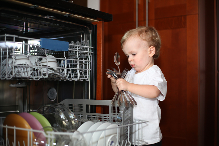 Little boy standing near the dishwasher taking forks and spoons out of it. Playing with cutlery. Baby boy and dishwasher. Baby proofing. Dishwasher with an open door and little boy playing with it. Little helper. Danger of household items for babies.