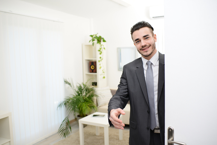 young businessman at the doorway giving hand to customer