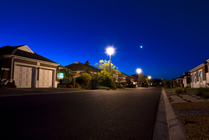 Urban night scene showing a road and various houses in a clear sky