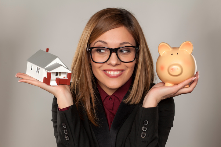 beautiful happy woman holds a model house and a piggy bank