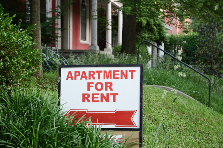 Apartment for rent sign displayed on residental street. Shows demand for housing, rental market, landlord-tenant relations.