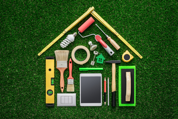 Home renovation, remodeling and DIY concept, work tools and tablet composing a house shape on the grass